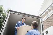 stock photo of moving van  - Movers unloading a moving van and passing a cardboard box - JPG