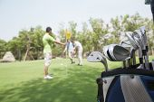 image of caddy  - Three friends playing golf on the golf course - JPG