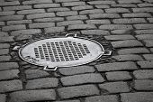 picture of manhole  - Old sewer manhole on dark cobblestone pavement - JPG