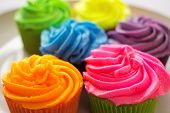 picture of icing  - Many bright colorful cupcakes on a white plate.