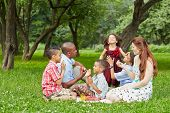 foto of mulatto  - Happy family of six takes rest at picnic in summer park - JPG
