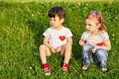 Two little children sit on grassy slope, red hearts pinned to theirs shirts