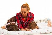 image of pyjama  - Mother in pyjamas looking at her sleeping kids - JPG
