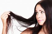stock photo of frustrated  - brunette woman is not happy with her fragile hair - JPG
