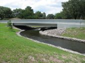 pic of sedimentation  - Large drainage canal flowing under street bridge - JPG