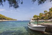 stock photo of deserted island  - Boats in a tranquil coast lagoon at a beach on Hvar Island - JPG