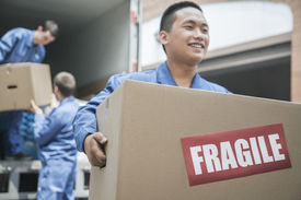 stock photo of fragile  - Movers unloading a moving van and carrying a fragile box - JPG