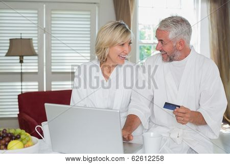 Happy mature couple doing online shopping through laptop and credit card at home