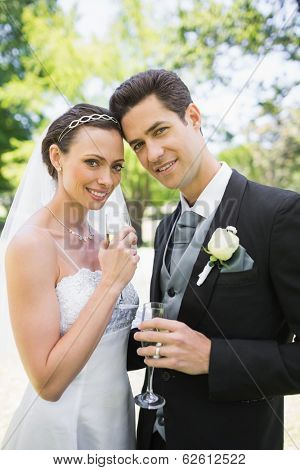 Portrait of beautiful bride and groom holding champagne flutes in park