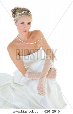 Portrait of sensuous bride sitting against white white background