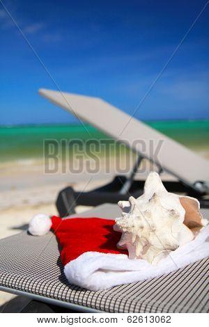 Santa Hat And Seashell On Chaise Longue On Beach