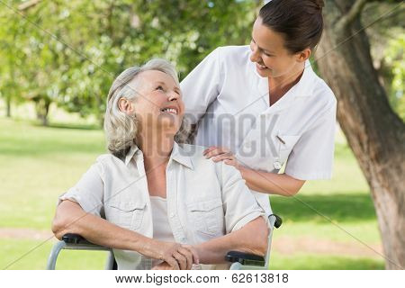 Portrait of a woman with her mature mother sitting in wheel chair at the park