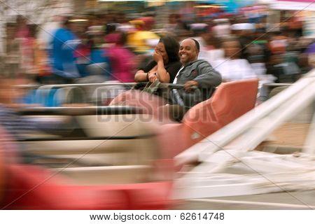 Couple Laughs Riding Scrambler Carnival Ride At Atlanta Fair