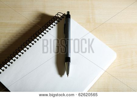 Notebook with pen on color wooden background
