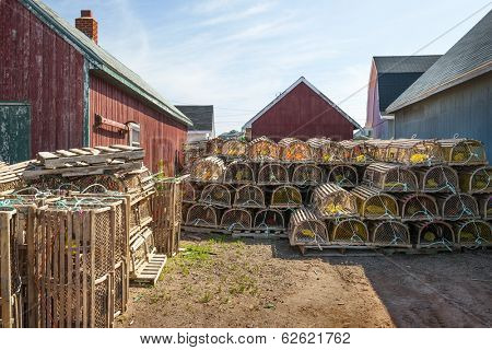 Stacks of wooden lobster traps between rustic buildings in North Rustico, Prince Edward Island, Canada