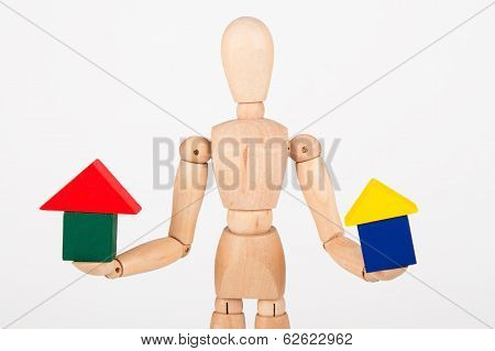 Small Wood Mannequin Sit Holding Colourful Block House Isolated On White