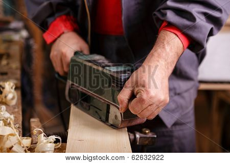Joiner With A Belt Sander On A Wooden Board