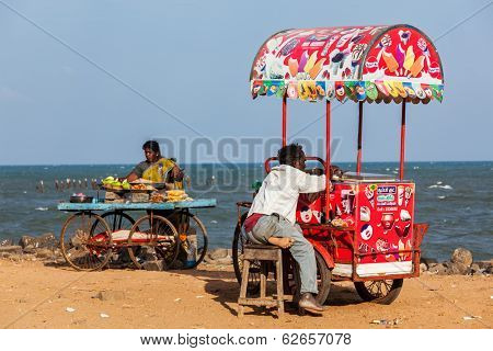 PONDICHERRY, INDIA - FEBRUARY 2, 2013: Unidentified Indian street vendors of ice cream and snacks with wheel carts on beach