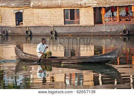 KERALA, INDIA - MAY 5, 2010: Unidentified indian man in small boat in backwaters. Kerala backwaters are both major tourist attraction and integral part of local people life in Kerala