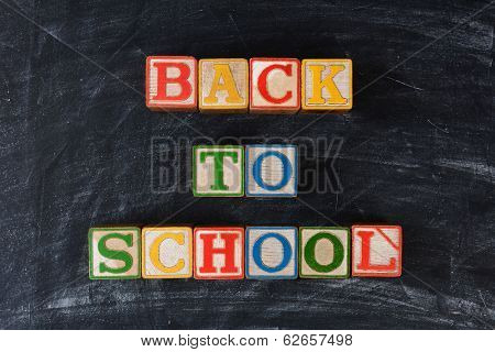 Childrens blocks spelling out Back To School on a chalk board. Horizontal format.