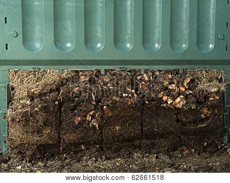 Closeup of green plastic compost bin with lower part removed to show advanced soil decomposition process