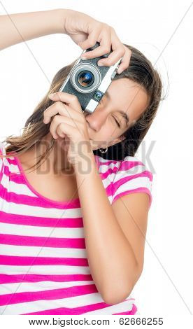 Fun happy young girl taking a photo with a vintage looking compact camera looking through the viewfinder (isolated on white)