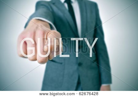man wearing a suit pointing the finger to the word guilty written in the foreground