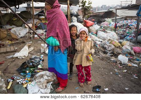 KATHMANDU, NEPAL - DEC 19, 2013: Unidentified children and parents are working on dump. In Nepal annually die 50,000 children, in 60% of cases -malnutrition.
