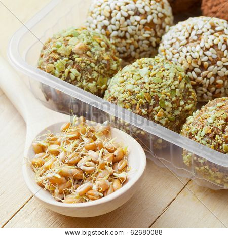 Balls From Ground Wheat Sprouts With Sesame And Green Pumpkin Seeds Sprinkles In Plastic Box; Sprout