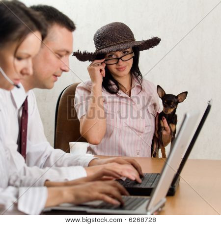 A Young Man And Woman Operatin Laptops And A Lady With A Dog