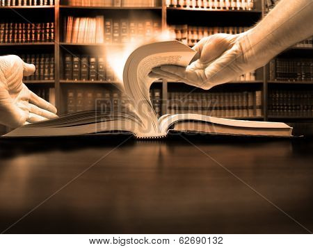 Hands turning pages in old book with library in background