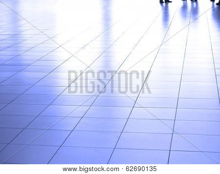 Several people walking across white marble tile floor