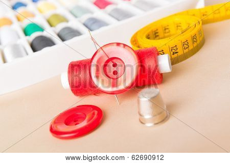 Reel of thread, buttons, thimble and other sewing accesories on the table