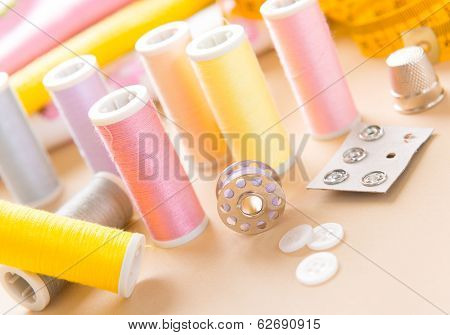 Reels of thread, buttons, thimble and other sewing accesories on the table