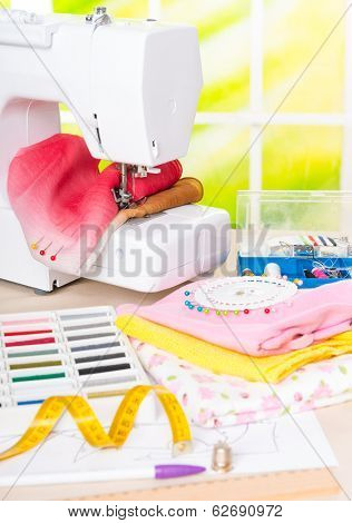 Sewing machine with colorful fabrics, threads, buttons, thimble and other sewing accesories.