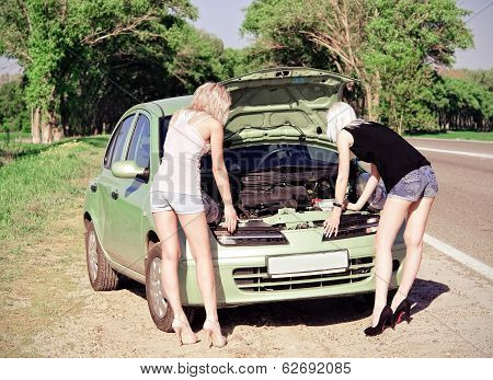 Two Blonde Girls Standing By The Broken Car