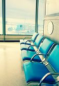 Empty armchairs in hall of expectation of airport and plane behind window with a retro effect