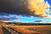 stock photo of pampa  - The enormous storm cloud and a flat plain covered in orange sunset - JPG