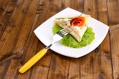 Pancake with salmon, and mayo, green onion, on plate, on wooden background