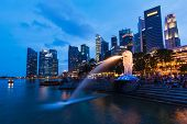 SINGAPORE - JANUARY 1, 2014: Night view of Singapore Merlion at Marina Bay against Singapore skyline