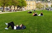 STUTTGART, GERMANY - APRIL 01, 2014: Young people rest on the grass in a Park near the Central squar