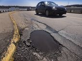 stock photo of tar  - Car avoiding big pot hole on urban street - JPG