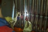Welder welding metal pipes