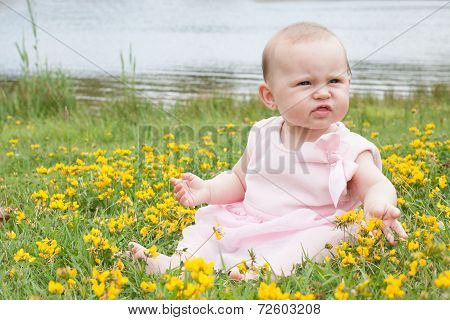 Baby Is Playing With The Flowers