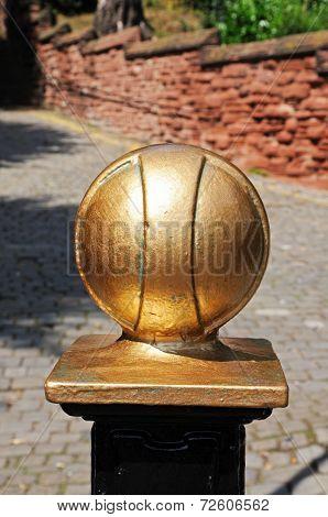 Gold ball on top of a fence post.