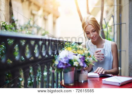 Pretty young woman reading book while sit at terrace table on her balcony