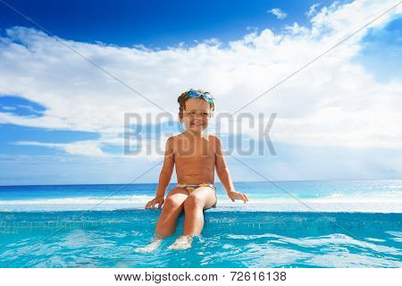Child sitting on stoned boarder with legs in water