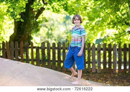 Cute School Boy Running On A Playground On A Hot Sunny Autumn Day