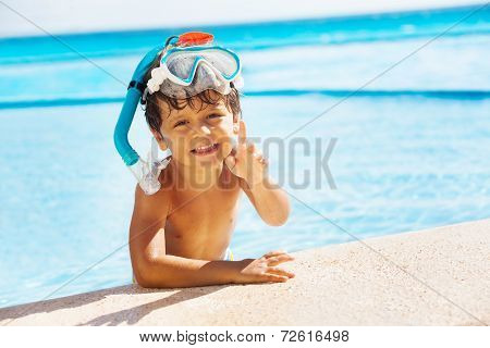 Boy with snorkel mask on head and pointing finger