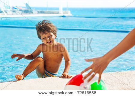 Laughing boy climbs up on boarder of pool to ball